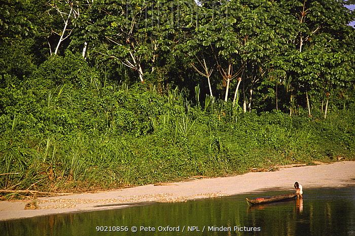Huaorani Indian pushing canoe along river, Dayuno, Ecuadorian Amazon, South America, 1994  -  Pete Oxford/ npl