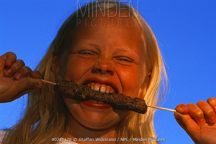 Girl eating grilled meat, Sweden  -  Staffan Widstrand/ npl