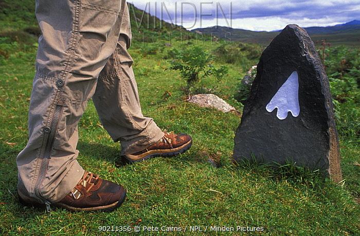 Legs of walker at a trailmarker, Wester Ross, Scotland, UK  -  Pete Cairns/ npl