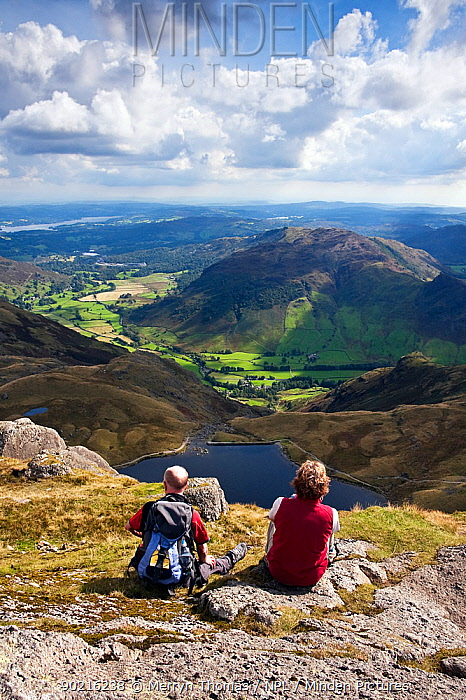 Couple looking out over Stickle Tarn and Great Langdale valley, from Pavey Ark Lake District, Cumbria, England September 2010  -  Merryn Thomas/ npl
