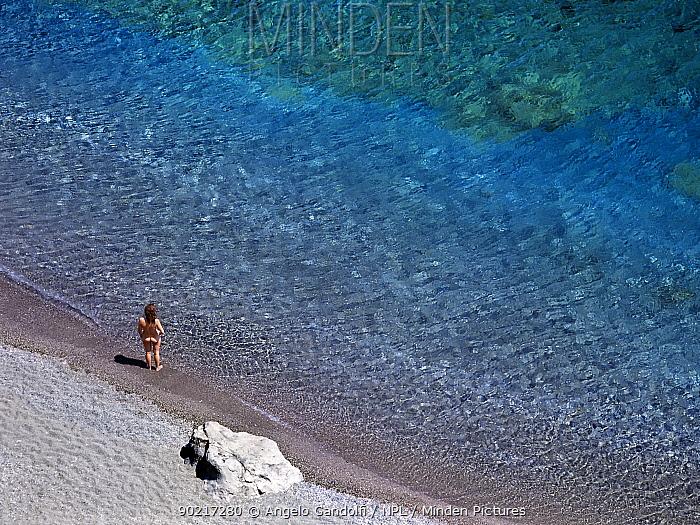 A woman standing on the shore, at the corner of Preveli beach, on the South coast of Crete, Greece  -  Angelo Gandolfi/ npl