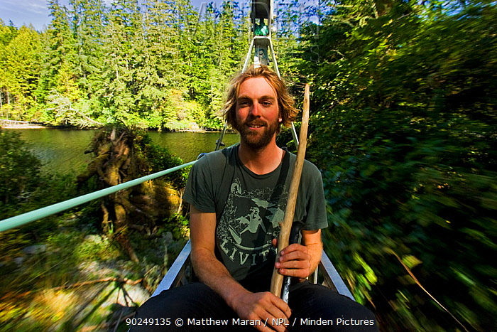 A man sitting in the cable car of a chair bridge as it crosses a river The West Coast Trail, Pacific Rim National Park, Vancouver Island, Canada, September 2010  -  Matthew Maran/ npl