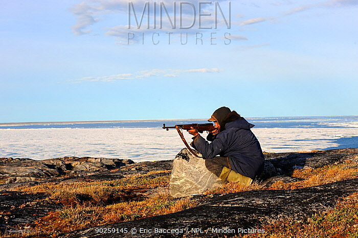 Inuit hunter aiming his gun in an icepack landscape Igloolik, Foxe Basin, Nunavut, Canada, July 2011  -  Eric Baccega/ npl