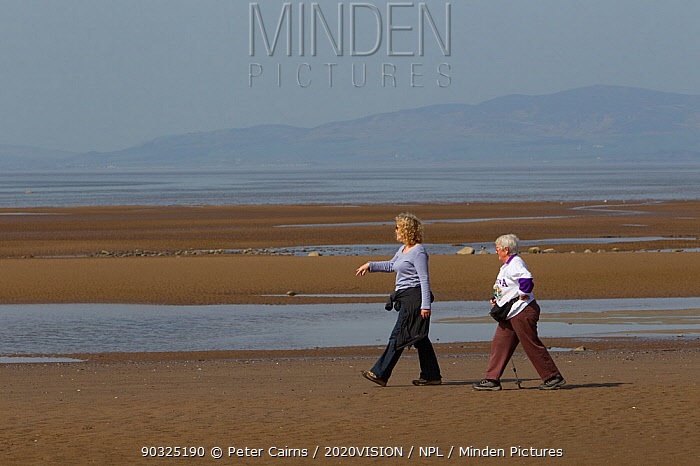 Two women walking along sandy beach at low tide, near Maryport, Solway Firth, Cumbria,UK, April 2011  -  Peter Cairns/ 2020V/ npl