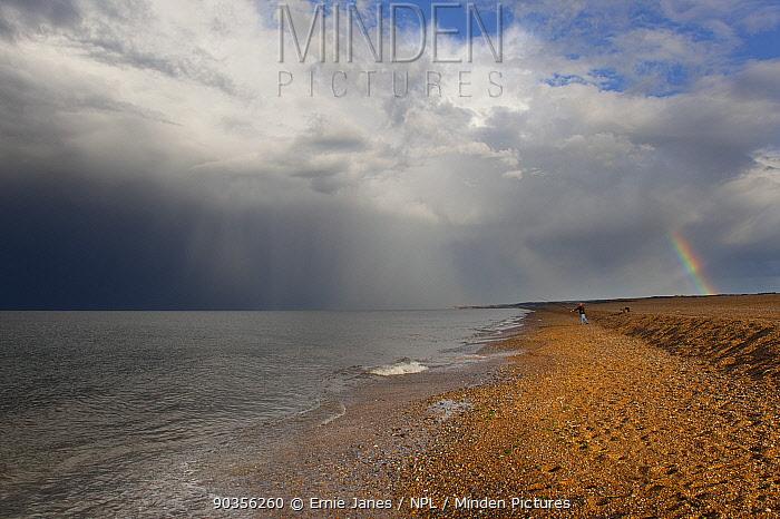 Shingle spit of Cley Beach with man fishing, Norfolk, UK  -  Ernie Janes/ npl