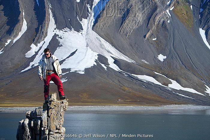 Field Assistant, Jason Roberts, standing on top of rock pinnacle, Svalbard, Spitzbergen, Norway, July 2009, Taken on location for the BBC series, Frozen Planet  -  Jeff Wilson/ npl