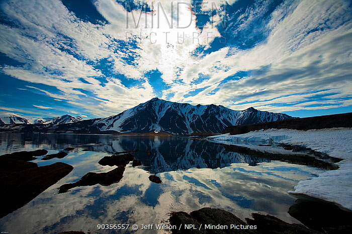 Sky and clouds reflected in melted Fjord in Svalbard, Sptizbergen, Norway, July 2009, Taken on location for the BBC series, Frozen Planet  -  Jeff Wilson/ npl