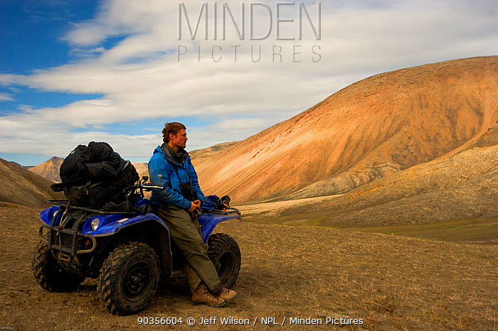 Director, Jeff Wilson, on an all-terrain-vehicle searching for Arctic Wolves, Ellesmere Island, Nunavut, Canada, June 2008 Taken on location for the BBC series, Frozen Planet  -  Jeff Wilson/ npl