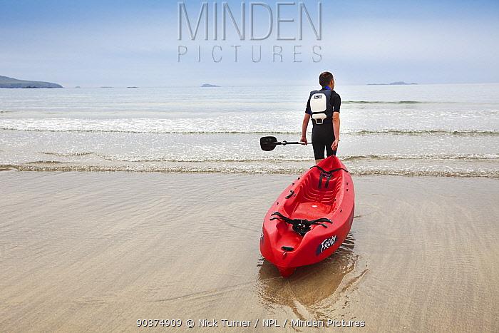 Man pulling his sea kayak into the sea at Caerfai Bay on the Pembrokeshire Coast Path, Wales, UK, June 2009  -  Nick Turner/ npl