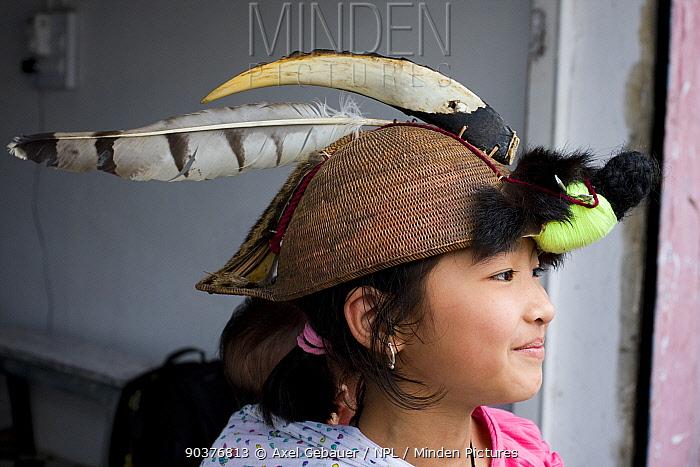 Girl wearing a hat with a hornbill lower mandibel, a raptor feather and civet fur, Tawang, Arunachal Pradesh, India 2008  -  Dr. Axel Gebauer/ npl