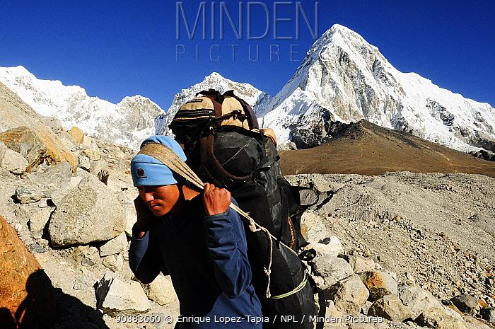 Porter carrying load across the Khumbu glacier with Pumori peak (7145m) in the background Sagarmatha National Park (World Heritage UNESCO) Khumbu, Everest Region, Nepal, Himalaya, October 2011  -  Enrique Lopez Tapia/ npl