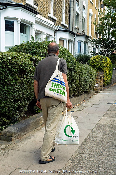 Man walking along urban street carrying two reusable cotton shopping bags with recycling logo printed on one and Think Green on the other, Holloway, London Borough of Islington, England, UK, September 2006  -  Pat Tuson/ npl