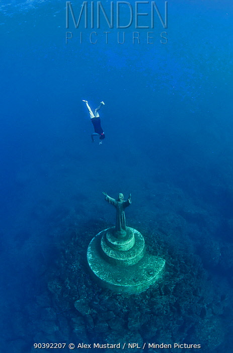 A fisherman swims down to toch the statue of Christ Of The Abyss (Cristo degli abissi) for good fortune, in the Marine Protected Area of Portofino (Area Marina Protetta, Portofino), Liguria, Italy Mediterranean Sea The statue was the world's first underwater statue, sculpted by Guido Galletti, and placed underwater in 1954 Its bronze consists of medals of mariners and athletes, parts of ships, bells and canons It was restored in 2004 There are two famous copies of this statue, one underwater in the Florida Keys and one underwater in Grenada  -  Alex Mustard/ npl