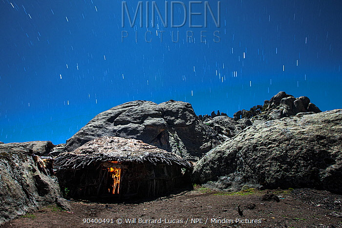 Cooking hut lit inside by a small cooking fire, with star trails, Bale Mountains National Park, Ethiopia, December 2011  -  Will Burrard-Lucas/ npl