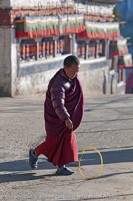 Young monk playing with homemade hoop toy during Torgya festival Galdan Namge Lhatse Monastery, Tawang, Arunachal Pradesh, India January 2014  -  Bernard Castelein/ npl