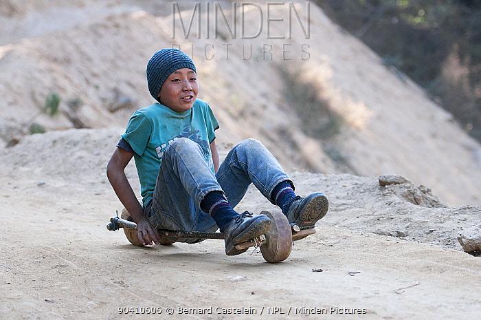 Boy playing with homemade slide toy on wheels Dirang, Arunachal Pradesh, India February 2014  -  Bernard Castelein/ npl
