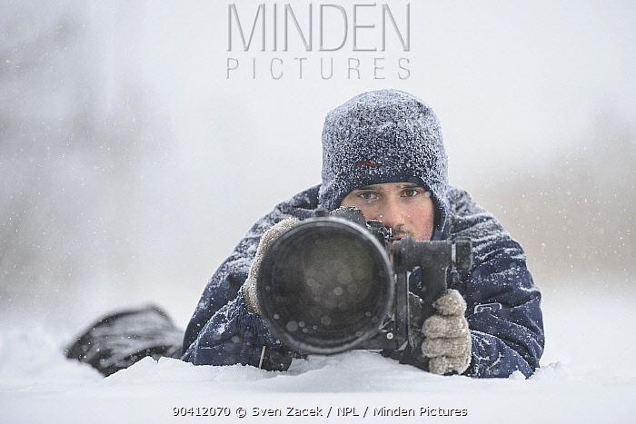 Photographer Sven Zacek with camera in the snow  -  Sven Zacek/ npl