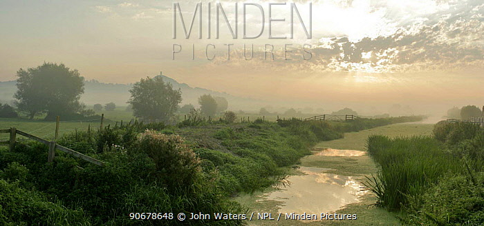 Glastonbury Tor, distant at misty early morning, with River Brue and meadows of the Somerset Levels, UK Digital Composite  -  John Waters/ npl