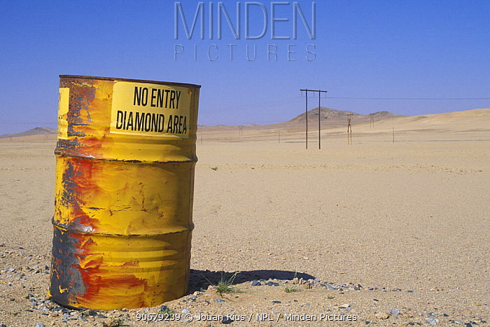 An old barrel at the diamond area border being used as a sign post warning people not to enter, Namib desert, Namibia  -  Jouan & Rius/ npl