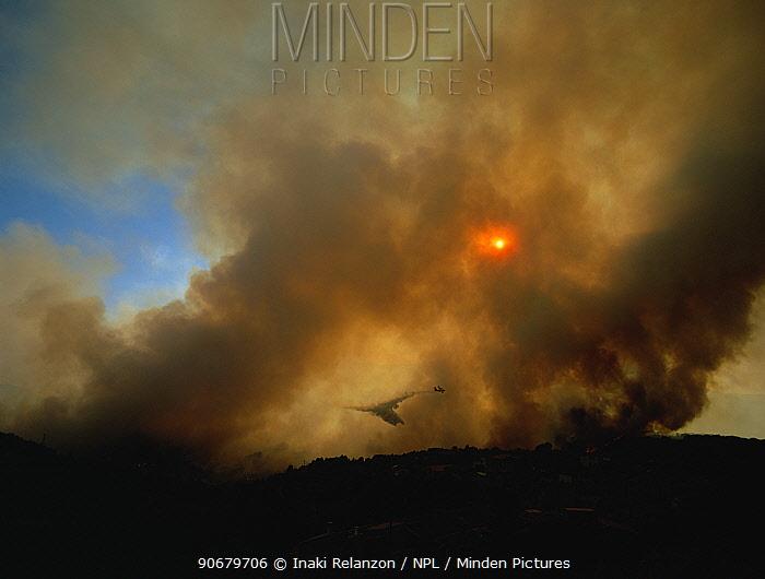 Dense smoke surrounds aeroplane dropping water, fire retardant on forest fire, Coll de Lilla, Tarragon, Spain, April 2004  -  Inaki Relanzon/ npl