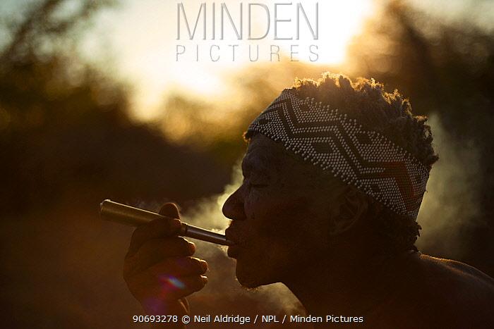A Zu, 'hoasi Bushman smokes a pipe made out of an old artillery cartridge at sunset in the Kalahari, Botswana April 2012  -  Neil Aldridge/ npl