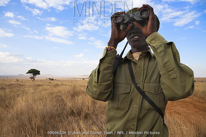 Member of the Rhino patrol, partly funded by Save the Rhino international, looks out using binoculars, Lewa Conservancy, Laikipia, Kenya, September 2012  -  Ann & Steve Toon/ npl