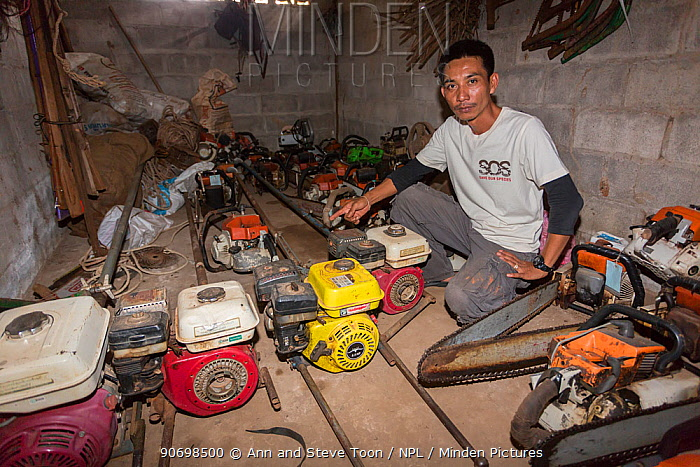 Sayan Raksachart of Freeland Foundation, with confiscated outboard motors and chainsaws used by Siam rosewood tree poachers, Thap Lan National Park, Dong Phayayen-Khao Yai Forest Complex, eastern Thailand, August, 2014  -  Ann & Steve Toon/ npl