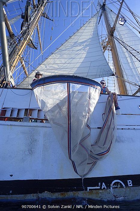 Scientists lowering plankton net to investigate marine microplastics, from Corwith Cramer,  a 134-foot steel brigantine.  Sargasso Sea, Bermuda, April 2014.