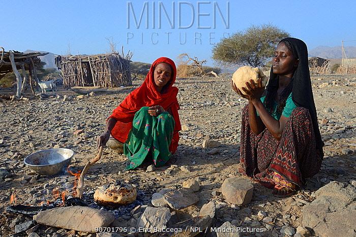 Afar tribe women baking bread with a hot stone on open fire, Malab-Dei village, Danakil depression, Afar region, Ethiopia, March 2015.