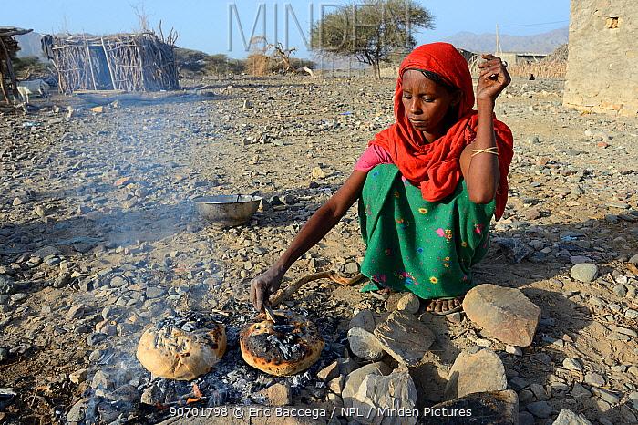 Afar tribe woman baking bread with hot stone on open fire, Malab-Dei village, Danakil depression, Afar region, Ethiopia, March 2015.