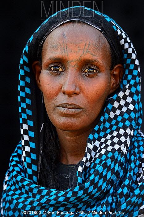 Head portrait of Afar tribe woman with facial tattoos / skin scarifications and wearing head scarf, Malab-Dei village, Danakil depression, Afar region, Ethiopia, March 2015.