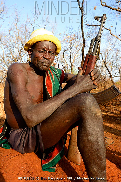 Older man from the Bodi tribe displaying elaborate skin scarifications, and holding Kalashnikov gun. The ones on his shoulder are for enemies he killed, the circles on the arm are for big game he hunted, Omo Valley, Ethiopia, March 2015.