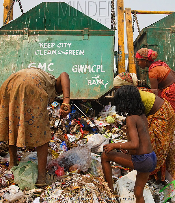 Rag picker women and children going through rubbish at landfill site,  Guwahti, Assam, India, March 2009.