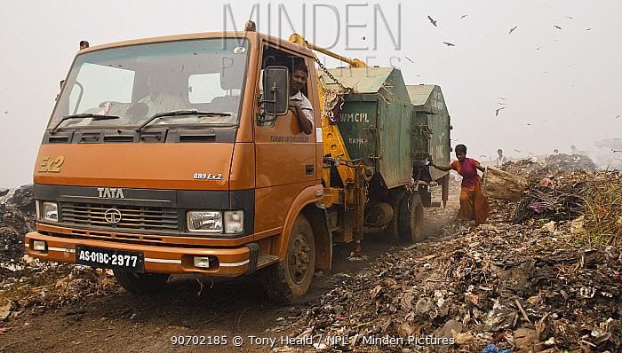 Rag-picker woman following inbound rubbish trucks at landfill site, Guwahti, Assam, India, March 2009.