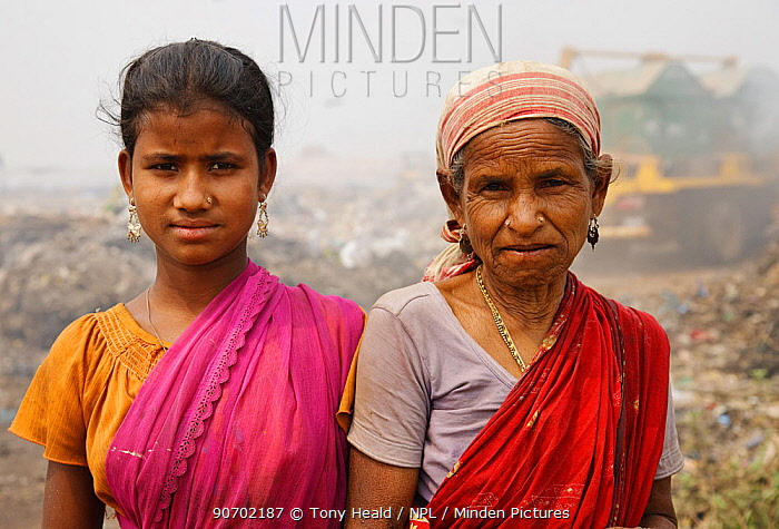 Rag-pickers, girl with elderly woman, at landfill site in, Guwahti, Assam, India, March 2009.
