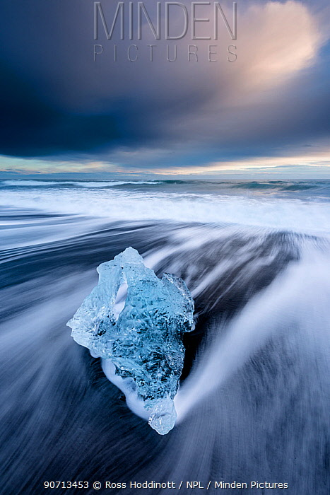 Ice on black volcanic sand beach with long exposure waves, Jokulsarlon, Southeast Iceland, February.