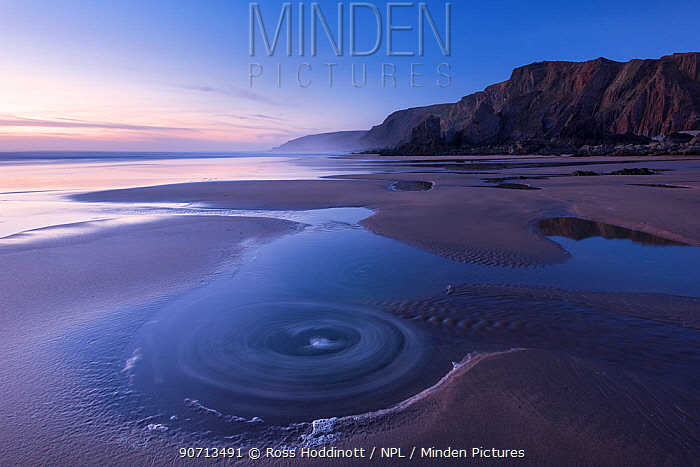 Long exposure of Sandymouth Bay, at dusk showing eddies in the water, Bude, Cornwall, UK. April 2015.