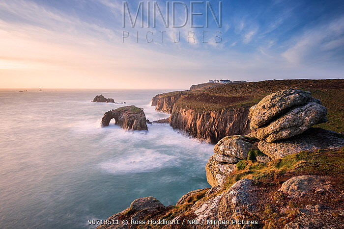 View towards Enys Dodnan Arch and the Armed Knight rock, Land's End, with Longships lighthouse in the distance, Cornwall, UK. March 2015.