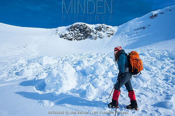 Hiker in winter weather gear walking on snowy mountainside in Cairngorms National Park, Scotland, March 2014.