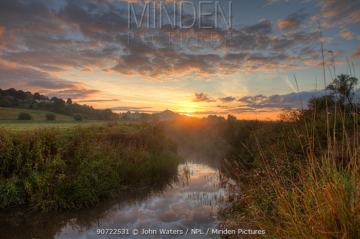 River Brue, at dawn with Glastonbury Tor in background,  Somerset, UK, August.