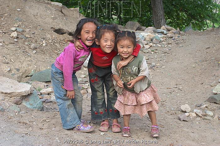 Group of local children smiling, near Lantsang Mekong river, Kawakarpo Mountain, Meri Snow Mountain National Park, Yunnan Province, China.