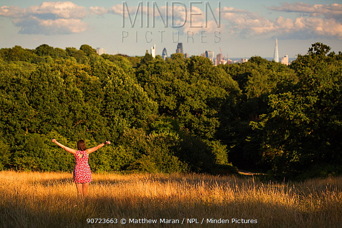 Visitor to Hampstead Heath with arms outstretched. Hampstead Heath, London, England, UK. July 2015.