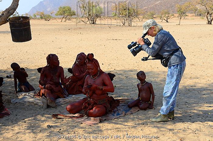 Woman filming daily life of Himba people, Marienfluss Valley, Kaokoland Desert, Namibia. October 2015