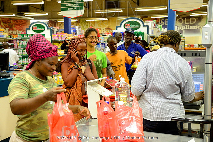 Himba woman in traditional clothing with cellphone and doing shopping at the supermarket, Opuwo, Kaokoland, Namibia. October 2015