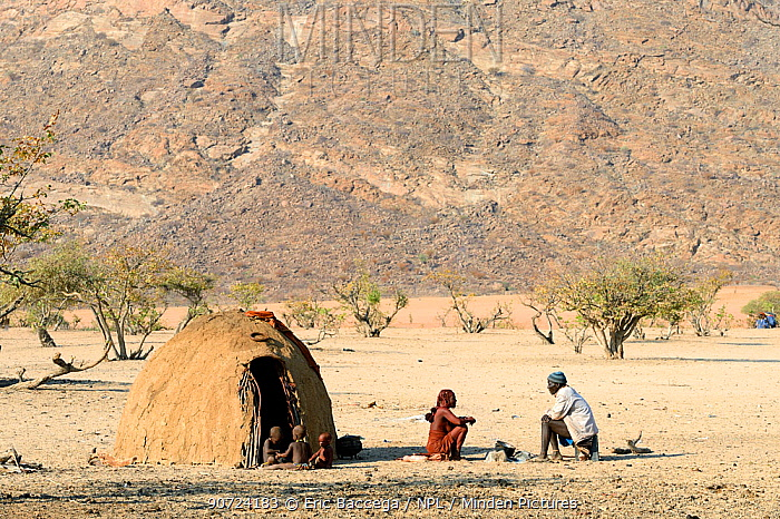 Himba family beside traditional mud hut, Marienfluss Valley during the dry season. Kaokoland, Namibia. October 2015