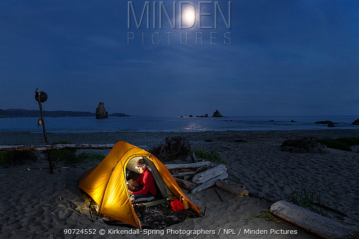 Moon rising over campsite, Toleak Point, Olympic National Park, Washington, USA. August 2015. Model released.