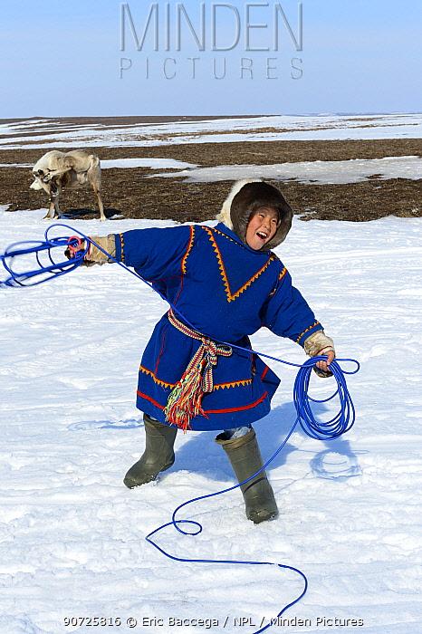 Nenet herder practising with lasso, wearing traditional malitsa coat. Yar-Sale district, Yamal, Northwest Siberia, Russia. April 2016.