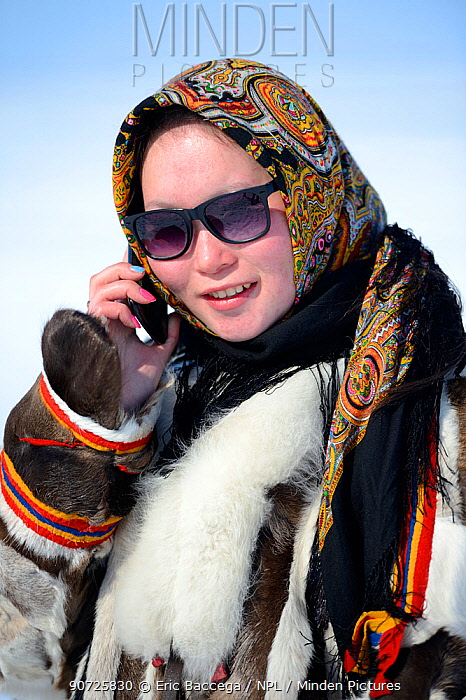 Carolina Serotetto, Nenet teenager wearing sunglasses and  traditional winter coat of reindeer fur holding smartphone. Yar-Sale district, Yamal, Northwest Siberia, Russia. April 2016.