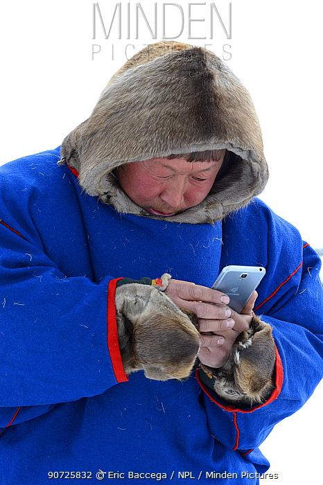 Nenet reindeer herder in traditional malitsa (reindeer skin coat) with smartphone. Yar-Sale district, Yamal, Northwest Siberia, Russia. April  2016.
