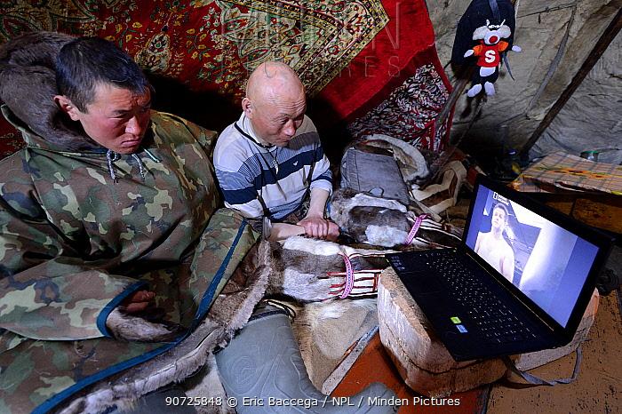 Nenet herders watching laptop inside tent. Yar-Sale district. Yamal, Northwest Siberia, Russia. April  2016.